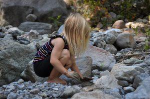 Mädchen beim Spielen am Bach mit Steinen